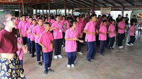 A group of cute Asian students have fun dancing during a school assembly in Ratchaburi, Thailand.