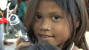 A cute little Thai girl playfully points a plastic gun at the camera in the slums of Bangkok, Thailand.
