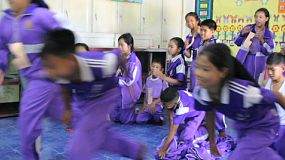 A group of Asian students take part in a fun relay race game while learning English with a group of young adult overseas missionaries in Chiang Rai, Thailand.
