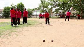 A group of Asian students enjoy a game of Bocci ball during a break at school in Buriram, Thailand.
