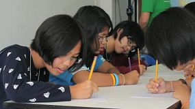 A group of young Asian students write an English exam at school in Phuket, Thailand.