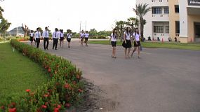 A group of male and female Asian university students stroll across the campus on their way to class in Thailand.