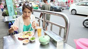 A beautiful Thai woman enjoys eating some delicious Thai food by the side of the street in Bangkok, Thailand.