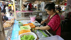 A food vendor preparing fresh spring rolls in a market in Bangkok, Thailand.
