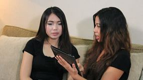An attractive Asian woman shows her friend how to use a digital PC tablet in her living room.