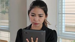 An attractive female Asian office worker uses her tablet at work in Bangkok, Thailand.