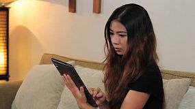 An attractive Asian woman uses her new digital PC tablet in her living room in Bangkok, Thailand.