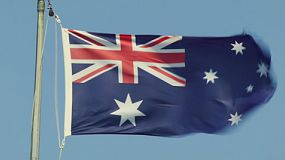 The Australian flag flying on a flagpole on a very windy day.