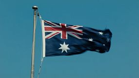 An Australian flag flying on a flagpole on a very windy day.