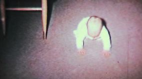 A cute baby boy learns to crawl on the living room floor with the help of his mother in 1964.