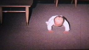 A cute little baby boy doing some commando crawling across the living room. (Vintage 8mm film)