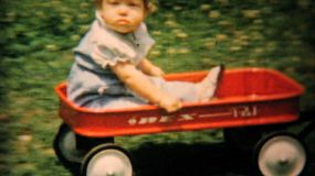 A cute baby girl is pulled around the back yard in her red wagon by her big brother in the summer of 1961.