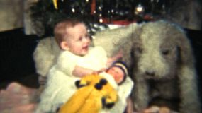 A cute red headed baby girl plays with her doll in front of the Christmas tree and her enormous stuffed puppy dog.