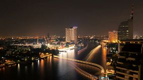 Time lapse view of the Chao Phraya River in Bangkok at night with light trails.