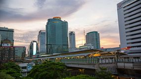 Time-lapse of the sun setting behind skyscrapers and a busy BTS skytrain station in Bangkok, Thailand.