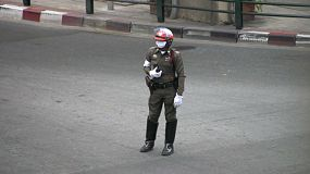 A Bangkok traffic police officer stands in the middle of an intersection directing traffic wearing his classic tight fitting brown uniform.