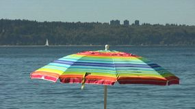Boats pass behind a rainbow colored beach umbrella by the ocean.