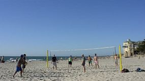A group of men playing beach volleyball on cottesloe beach, in perth, western australia.