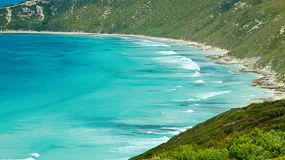 Looking across a beautiful bay with clear turquoise water, as waves roll in, near Esperance, Western Australia.