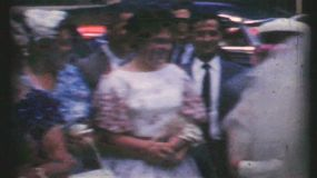 A beautiful bride and groom head to their getaway car after the big wedding in 1960.