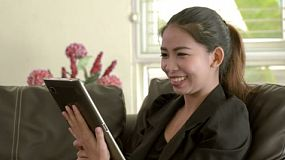 A young Asian businesswoman chatting to a friend on her tablet pc.