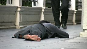 A beggar lays on the sidewalk begging as people casually walk by without a glance.