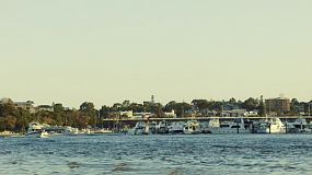 A small boat coming up the Swan River near Fremantle, Western Australia, past a yacht club.