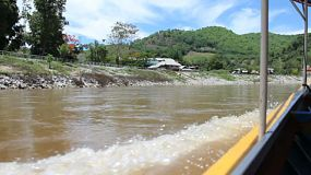 A long tail boat travels up river in the province of Chiang Rai, Thailand.