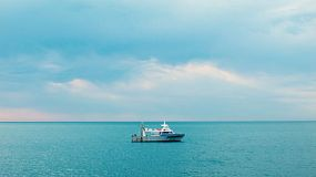 A fishing boat on the still blue ocean waters near Fremantle, Western Australia, on a cloudy day.