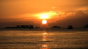 A lovely shot of several different kinds of boats anchored in Pattaya Bay, Thailand while the sun sets.