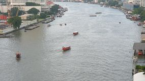 Lots of boats going up and down the Chaophraya River in Bangkok, Thailand.