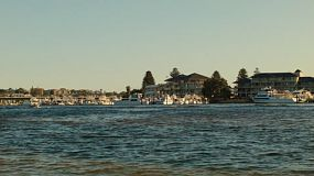 Late afternoon on the Swan River in Perth, Australia, with boats passing and moored at a yacht club.