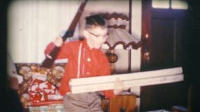A boy gets a brand new gun on Christmas Day in 1958.