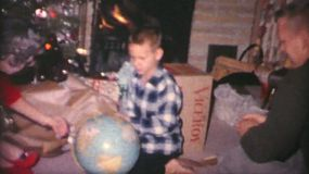 A young boy enjoys getting his new world globe on Christmas morning in 1962.