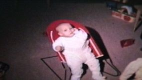 A cute little boy plays in his baby bouncer in the living room.
