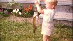 A cute little blond haired boy proudly displays the fish he caught while fishing with his Grandfather in the summer of 1967.