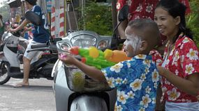 Bangkok, Thailand - April 14, 2014: A young Thai boy shooting his water pistol as his mother looks on with a smile, during the Songkran Festival in Thailand.
