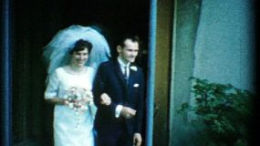 A happy bride and groom leave the church after their wedding and head to the getaway car in the summer of 1967.