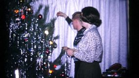 A brother and sister spend time together trimming the Christmas tree with tinsel in 1961.