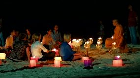 A Buddhist monk teaching by candlelight, on a beach in Thailand.