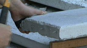 A construction worker tried to bend nails off a piece of concrete used to build a foot bridge.