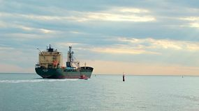 A bulk carrier ship leaving Fremantle Port, escorted by a tugboat, heading out to sea.