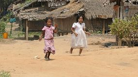 Cute Burmese children enjoying playing and running up a dirt road in the village just outside Myawaddy, Burma.