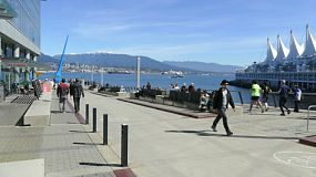 People enjoying a beautiful spring day near the Vancouver Convention Center across from Canada Place on the Burrard Inlet in the city of Vancouver.