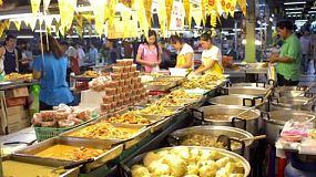 A busy night food market in Bangkok, Thailand, with ready made dishes laid out for people to order.