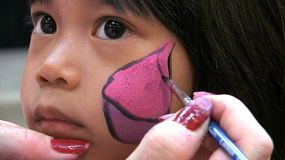A cute little Asian girl waits patiently while an artist paints a pretty pink butterfly on her face.