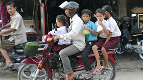 A young family stops for breakfast on their way to school in Phnom Penh, Cambodia.