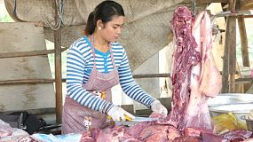 A pretty Khmer lady cuts and prepares fresh meat at her butcher shop by the side of the road in Phnom Penh, Cambodia.
