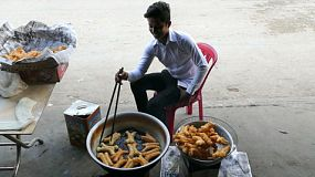 A Khmer man fries tasty donuts in the morning on the streets of Phnom Penh, Cambodia.