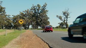 Cars passing by a kangaroo warning sign on a road in country Western Australia.